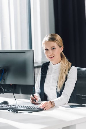 beautiful young businesswoman sitting at workplace and smiling at camera