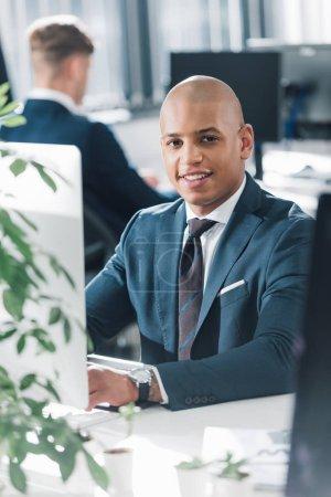 Photo pour Beau jeune entrepreneur africain-américain assis au milieu de travail et souriant à la caméra - image libre de droit