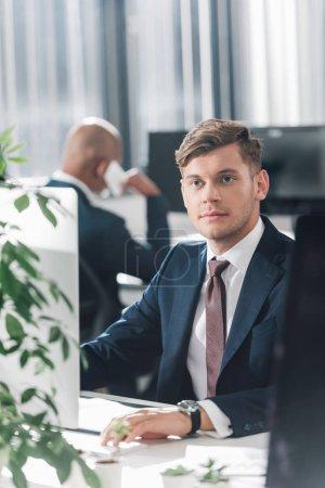 Foto de Empresario joven pensativo sentado en el lugar de trabajo y mirando lejos - Imagen libre de derechos