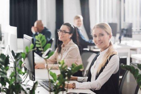 Photo pour Souriante jeune femmes chefs d'entreprise travaillant avec des ordinateurs en fonction de l'espace ouvert - image libre de droit