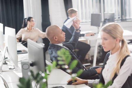 Photo pour Jeune homme d'affaires américain jouant avec avion de papier tandis que les collègues travaillant dans les bureaux - image libre de droit