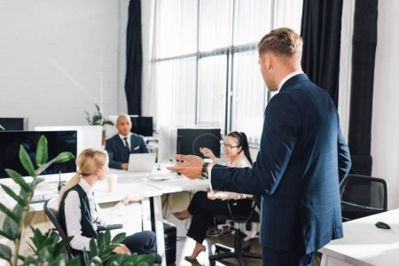 young businessman gesturing and talking with colleagues in open space office
