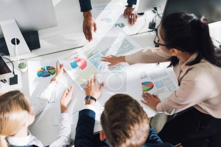 Photo for High angle view of young business team working with charts and graphs in office - Royalty Free Image