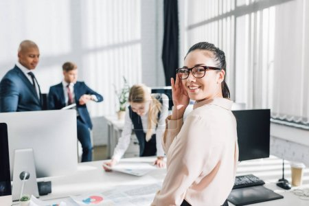 attractive young businesswoman in eyeglasses smiling at camera while working with colleagues in office