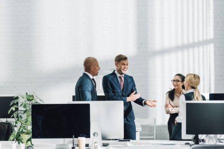 Foto de Empresario joven emocional hablando con colegas de trabajo - Imagen libre de derechos