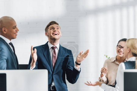 Photo for Happy young business colleagues talking at workplace - Royalty Free Image