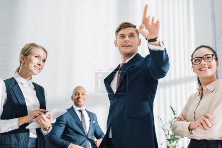 Photo pour Collègues souriants regardant jeune homme d'affaires pointant du doigt dans le bureau - image libre de droit