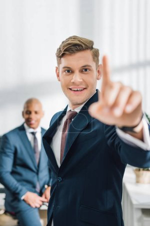 handsome young businessman pointing with finger and smiling at camera