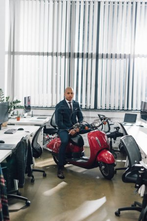 handsome young african american businessman sitting on red scooter and looking at camera in office