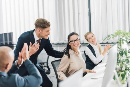 smiling young coworkers greeting and applauding to happy female colleague in office