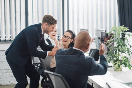 happy young business colleagues laughing and applauding at workplace