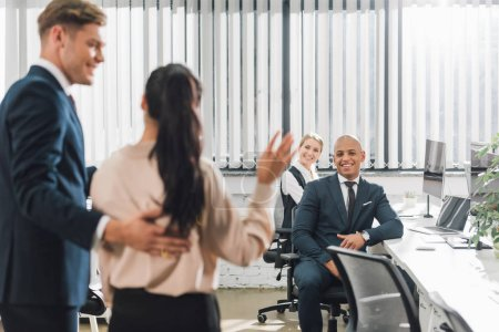 smiling businessman looking at new colleague waving hand and greeting coworkers in office