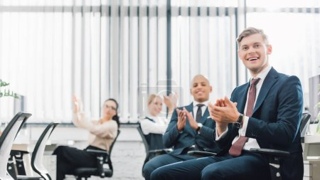 happy young multiethnic business colleagues applauding in office