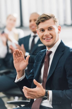 happy young businessman waving hand and smiling at camera in office