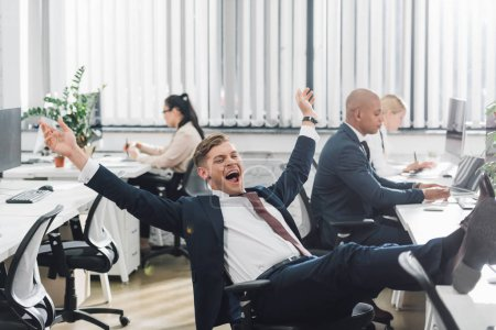 excited young businessman triumphing while working in office