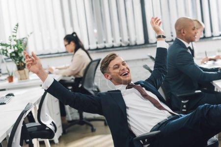 Foto de Excitada joven hombre de negocios triunfando mientras trabajaba en la oficina de espacios abiertos - Imagen libre de derechos