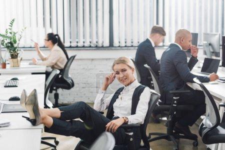 Photo pour Belle jeune femme d'affaires souriant à la caméra tandis que collègues travaillant derrière en fonction de l'espace ouvert - image libre de droit