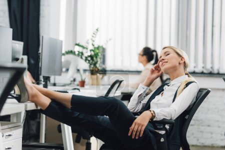 smiling young businesswoman resting with closed eyes at workplace