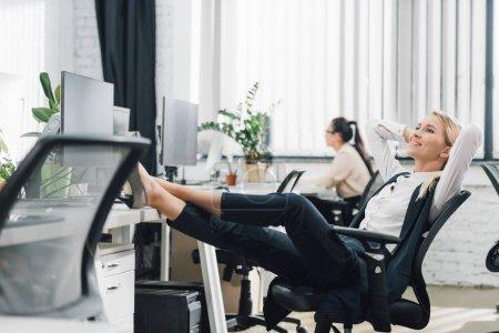 Photo pour Souriante jeune femme d'affaires au repos avec les jambes sur le bureau dans le Bureau - image libre de droit