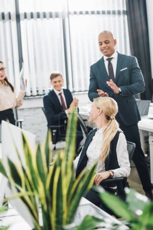 happy young colleagues applauding to smiling businesswoman in office