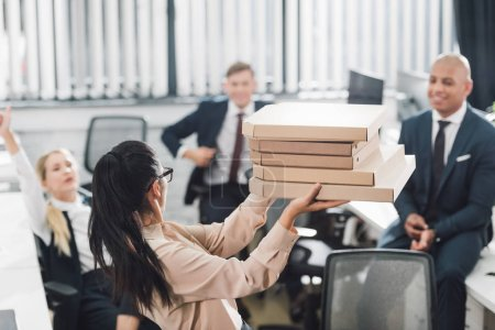 young businesswoman showing pizza boxes to happy colleagues in open space office