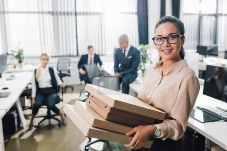 young businesswoman holding pizza boxes and smiling at camera while colleagues sitting behind in office