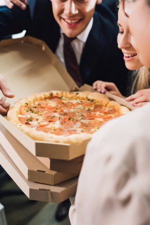 cropped shot of smiling young coworkers looking at tasty pizza in office