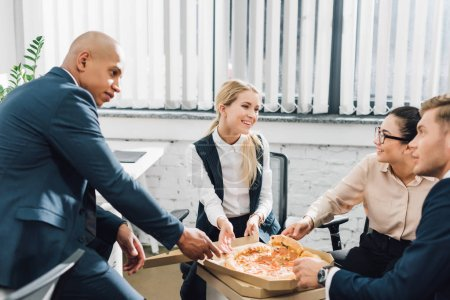 happy young business people eating pizza together in office