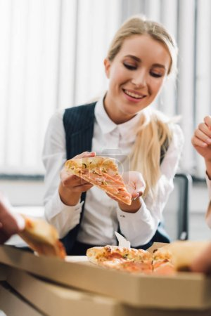 Photo for Smiling young businesswoman eating pizza with colleagues in office - Royalty Free Image