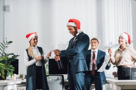 happy african american businessman in santa hat opening bottle of wine while celebrating xmas with colleagues in office