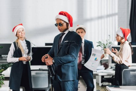 young african american businessman in santa hat and sunglasses opening bottle of wine while celebrating christmas with coworkers in office