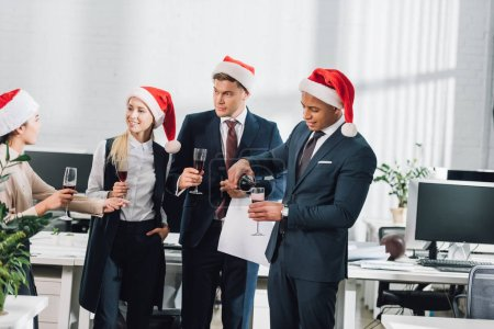 smiling young multiethnic coworkers in santa hats celebrating christmas in office