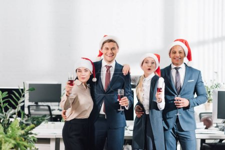 Photo for Happy young multiethnic coworkers holding glasses of wine and smiling at camera while celebrating new year in office - Royalty Free Image