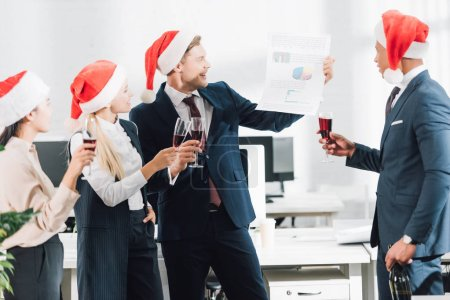 happy young multiracial business people in santa hats celebrating christmas in office