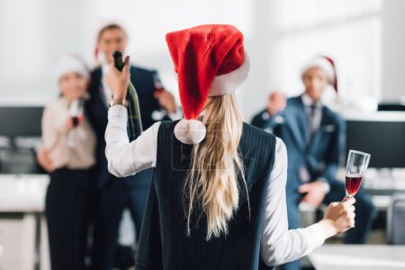 back view of businesswoman in santa hat holding glass and bottle of champagne while celebrating christmas with colleagues
