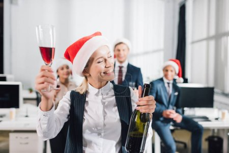 happy young business people in santa hats drinking wine and celebrating xmas in office