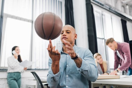 low angle view of young african american man playing with basketball ball in office