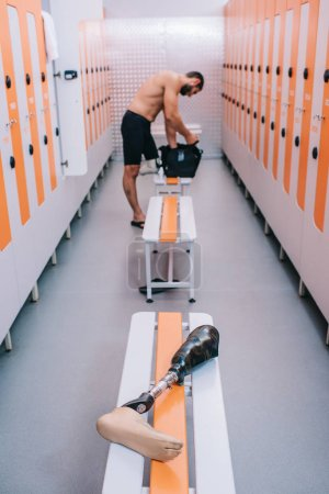 young sportsman with artificial leg at changing room of gym