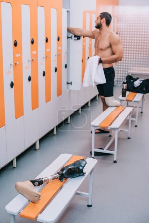 athletic young sportsman with artificial leg at changing room of swimming pool