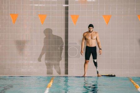 musculaire sportif jeune avec une jambe artificielle en regardant piscine couverte