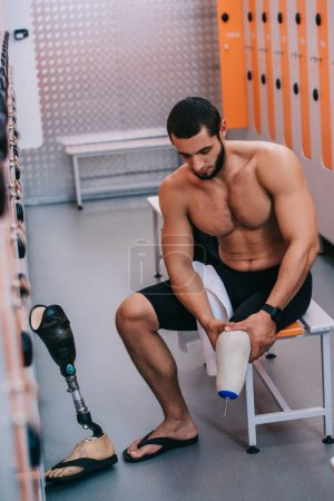 muscular young sportsman with artificial leg sitting on bench at changing room of swimming pool
