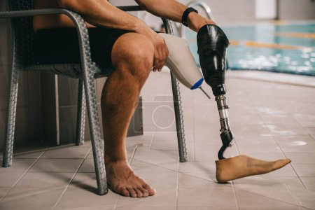 Photo for Cropped shot of sportsman with artificial leg sitting on chair at indoor swimming pool - Royalty Free Image