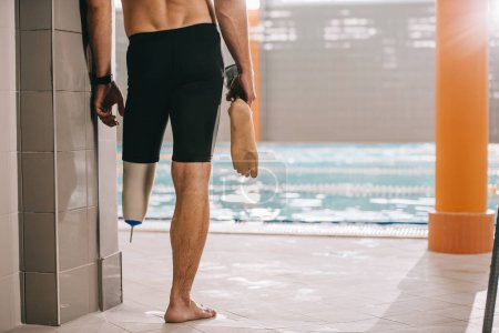 cropped shot of athletic swimmer standing at poolside of indoor swimming pool and holding his artificial leg