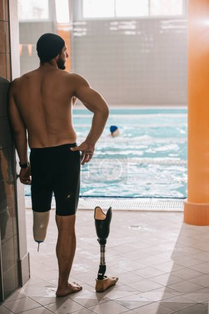 Photo for Rear view of swimmer standing at poolside of indoor swimming pool and taking off artificial leg - Royalty Free Image