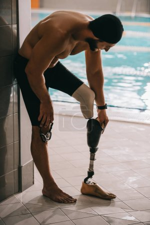 handsome swimmer standing at poolside of indoor swimming pool and taking off artificial leg