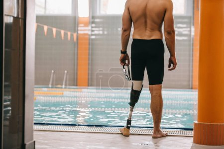 Photo for Cropped shot of sportsman with artificial leg standing in front of indoor swimming pool - Royalty Free Image