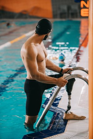 muscular young swimmer with artificial leg getting out of swimming pool