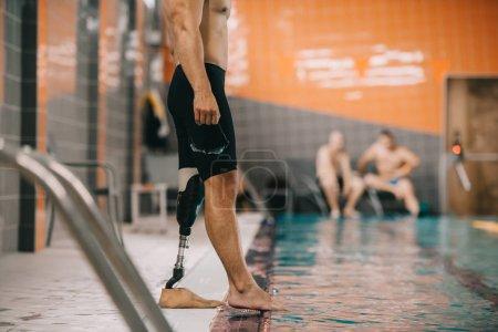 Photo pour Recadrée tir sportif musclé avec debout jambe artificielle sur le bord de la piscine à la piscine intérieure et contrôle température de l'eau - image libre de droit