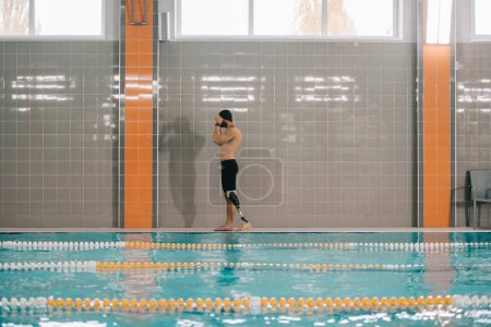 handsome young sportsman with artificial leg standing on poolside at indoor swimming pool