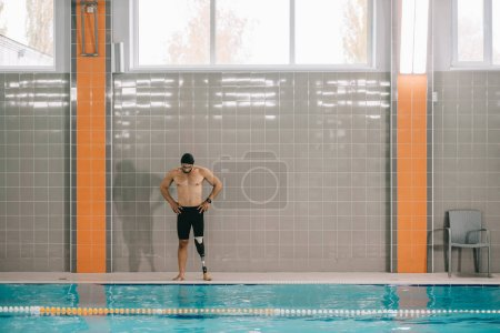 muscular young sportsman with artificial leg standing on poolside at indoor swimming pool